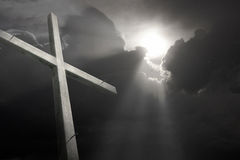 Wooden Cross faded againt Breaking Storm symbolizing Good Friday Stock Photo