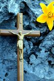 Crucifix on a porous rock with a yellow lily stock photography