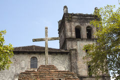 Wooden cross in front of old rustic church Royalty Free Stock Image