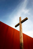 Wooden cross in front of rusty iron wall Stock Photography
