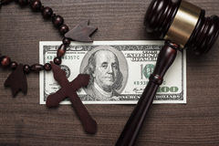 Wooden cross gavel and money on brown table Stock Image