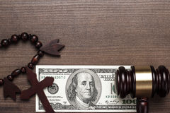 Wooden cross gavel and money on brown table background Stock Photo