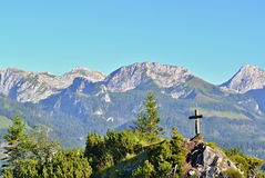 Wooden cross on a green peak with big mountains in background Stock Images