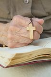 A wooden cross in the hand of senior woman. A hand of senior woman with wooden cross on a franciscan prayer book royalty free stock photos