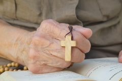 A wooden cross in the hand of senior woman Stock Photo