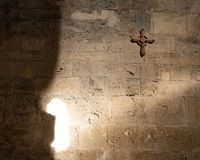 Wooden cross hanging on an old stone wall in a church, partially lit with sun rays stock image