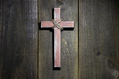 Wooden cross hanging on rustic wooden background