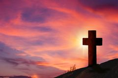 Wooden cross on hill with beautiful landscape in background.