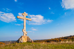Wooden cross on hill. Religious wooden cross on a hill against the blue sky royalty free stock photo
