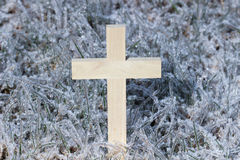 Wooden cross with ice covered grass background Royalty Free Stock Photos