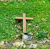 Fallen wooden Cross. Wooden cross laying in grass in churchyard Royalty Free Stock Photography