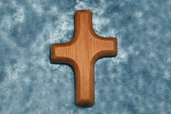 Wooden cross on light blue satin. Hand carved wooden cross on light blue satin royalty free stock image