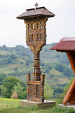 Wooden cross from Maramures, Romania. Traditional wooden carved cross from the Maramures area in Romania. In the background a beautiful landscape with haystacks Stock Images