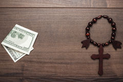 Wooden cross and money on brown table background Royalty Free Stock Photography