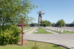 The wooden cross and Motherland calls!. VOLGOGRAD, RUSSIA - July 06, 2016: A wooden cross and a monument the Motherland calls! Soldier's cemetery. Museum Stock Photography