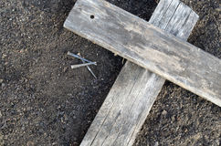 Wooden Cross With 3 Nails On The Ground. Wooden Cross with side lighting laying on the ground with 3 nails nearby Stock Photos