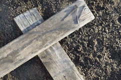 Wooden Cross With 3 Nails On The Ground. Wooden Cross with side lighting laying on the ground with 3 nails nearby Royalty Free Stock Photography