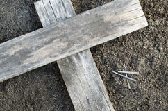 Wooden Cross With 3 Nails On The Ground. Wooden Cross with side lighting laying on the ground with 3 nails nearby Royalty Free Stock Image