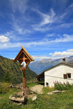 Wooden cross near rural house in Alps. Royalty Free Stock Image