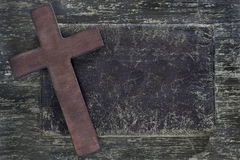 Wooden cross and old leather on  wooden board Stock Photos