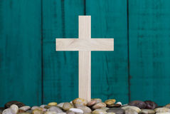 Wooden cross in pile of stones by antique teal blue wood background Royalty Free Stock Photo