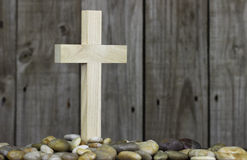 Wooden cross in pile of stones with rugged wood background Royalty Free Stock Photos