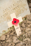 Wooden cross with a poppy for remembrance. Remembrance cross with poppy at the foot of a grave of an unknown British soldier of the First World War Royalty Free Stock Images