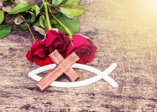 The wooden cross with red roses  on wooden table Royalty Free Stock Photo
