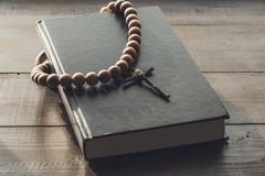 Wooden Christian Cross on the Closed Bible. A wooden cross with a rosary on a closed Holy Bible. The way to God through prayer. Closed book with a black cover royalty free stock photo