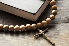 Wooden Christian Cross next the Closed Bible. A wooden cross with a rosary next a closed Holy Bible. The way to God through prayer. Closed book with a black royalty free stock photography