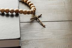 Wooden Christian Cross next the Closed Bible. A wooden cross with a rosary next a closed Holy Bible. The way to God through prayer. Closed book with a black stock images
