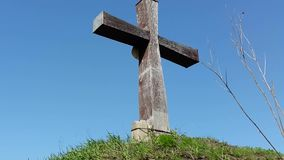 Wooden cross on the sky background. Big Wooden Cross is Standing among the Trees on the background of Blue Sky and Moving Clouds stock video