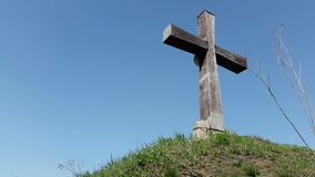 Wooden cross on the sky background. Big Wooden Cross is Standing among the Trees on the background of Blue Sky and Moving Clouds stock footage