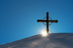 Wooden cross on snow capped mountain hill Royalty Free Stock Photos