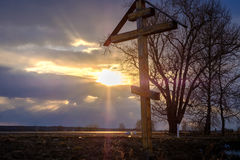 A wooden cross at sunset. In a field Royalty Free Stock Images