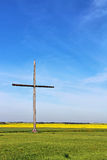 A wooden cross. Surrounded by grass and a yellow canola field against a blue wispy sky Stock Image