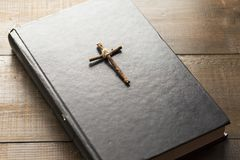 Wooden Christian cross on the Bible. A wooden cross tied with a thread on the closed Holy Bible. A black book on a wooden surface. The way to God through prayer stock photography