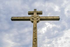 A wooden cross on top of a hill. Orthodox white cross glows on the top of the hill on the background of blue sky. And of green grass Royalty Free Stock Images