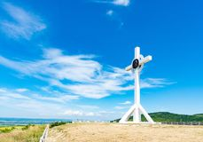 A wooden cross on top of a hill. Orthodox white cross glows on the top of the hill on the background of blue sky and of green gras. S stock photos