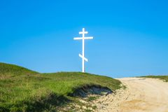 A wooden cross on top of a hill. Orthodox white cross glows on the top of the hill on the background of blue sky. All roads lead to God Royalty Free Stock Images