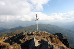 Wooden cross on top of a rocky hill Royalty Free Stock Images