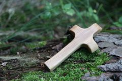 Wooden cross with tree on a green natural background Royalty Free Stock Photo