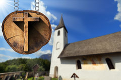 Wooden Cross on Tree Trunk with Small Church Stock Images