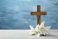 Wooden cross and white lily. On table Royalty Free Stock Photography