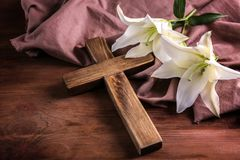 Wooden cross and white lily. On table Stock Photo