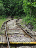 Wooden crossing over railroad tracks. Close-up of a wooden people crossing over railroad tracks which are curving away in to the trees royalty free stock photos