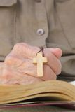 A wooden crucifix in the hand of senior woman Royalty Free Stock Image