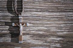 Wooden Crucifix Pendant. Wooden Catholic Crucifix pendant on the wooden floor Royalty Free Stock Photo