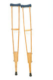 Wooden crutches rest on wall Royalty Free Stock Photography