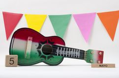 Wooden cube calendar with Cinco de Mayo date, toy guitar and colorful flags. On white background